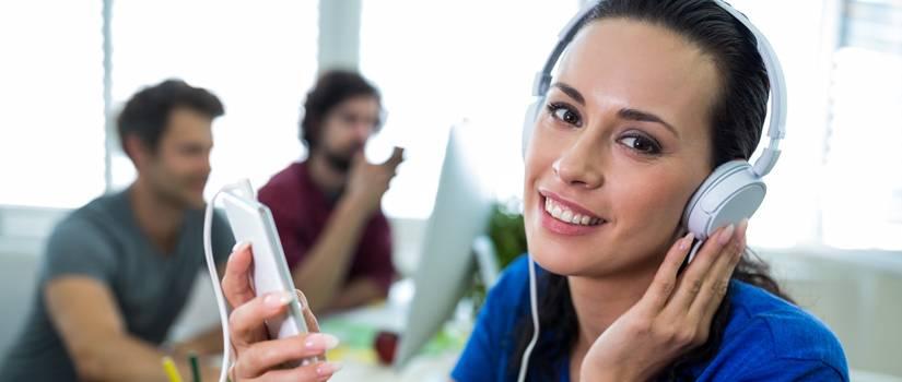 Female graphic designer listening music from mobile phone