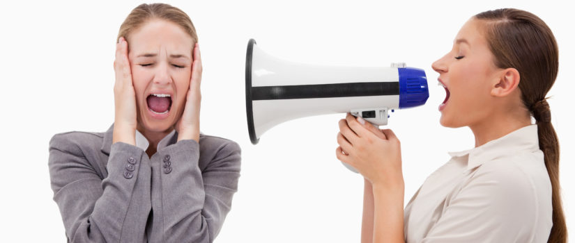 Young manager yelling at her employee through a megaphone against a white background