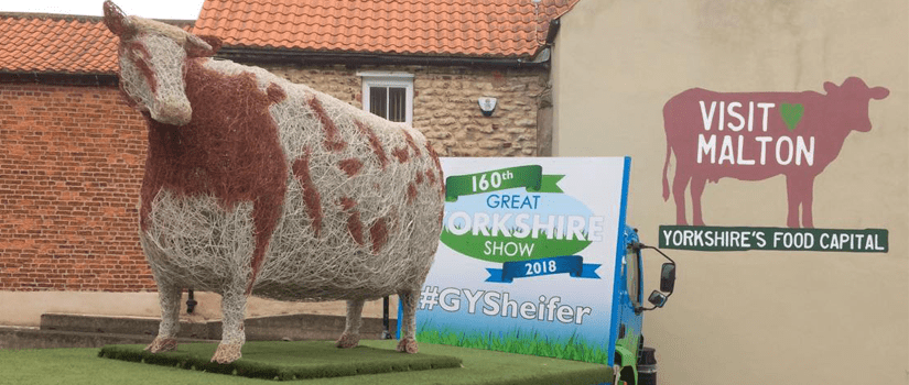 An image from Malton Food Festival, showing a cow made out of straw and a poster advertising the Great Yorkshire Show.