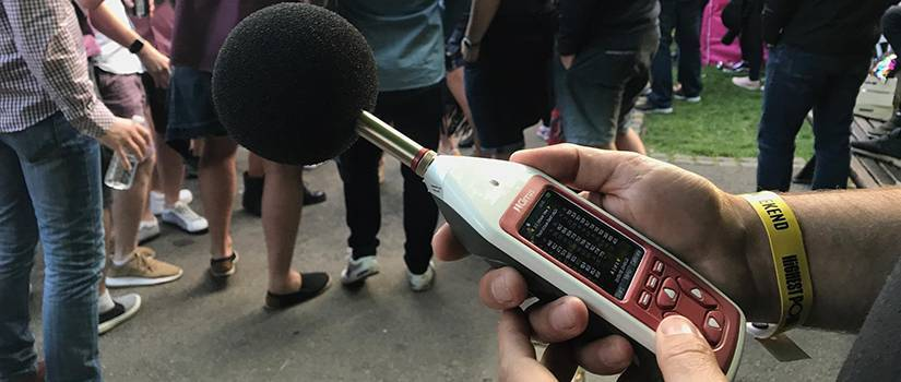 An image of a man holding an Optimus Green sound level meter, recording the noise levels of a music festival performance.
