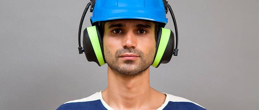 An image showing a man wearing PPE including ear defenders and a hard hat