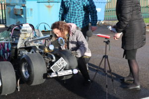 An image of junior drag racing champion, Caitlin Wilson, checking the status of her drag racer.