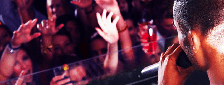An image showing a DJ stood in a DJ booth at a nightclub, in front of a group of young partygoers