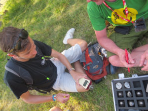 An image showing two young men, sat on a patch of grass at the Glastonbury music festival. They are holding doseBadge noise dosimeters from Cirrus Research